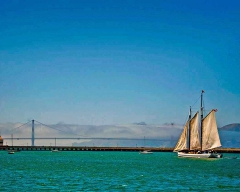 A sailing vessel on the San Francisco Bay with the Golden Gate Bridge in the background.
