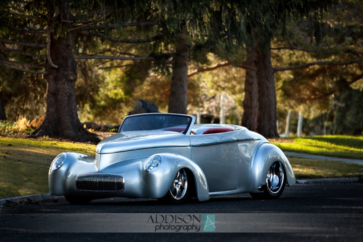 A silver '41 Willys Roadster outdoors in the fading sunlight.