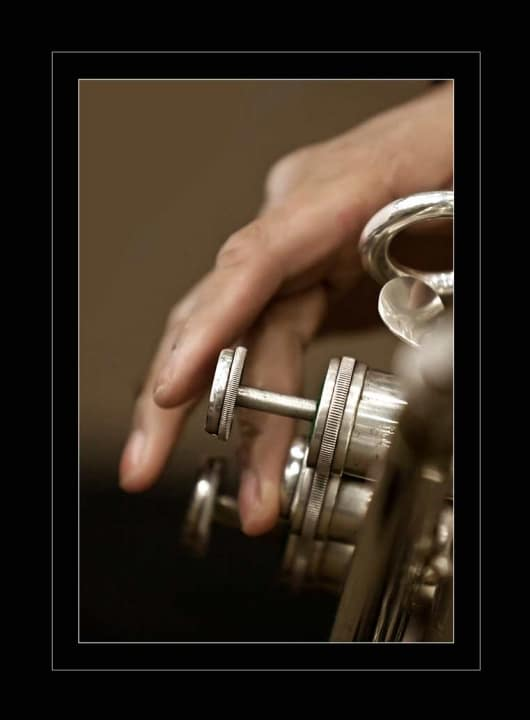 A close up of a working man's hands playing a trumpet.