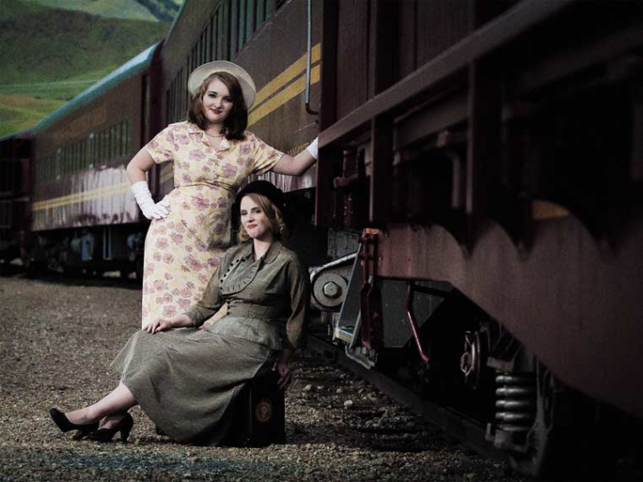 Two models in 1940's periond dresses posing at the train station.